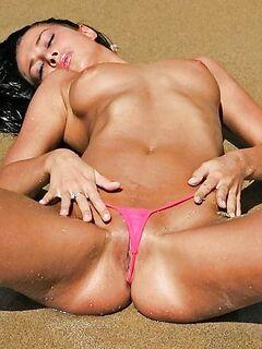 Загорелая красотка в розовых стрингах нежится на пляже - секс порно фото