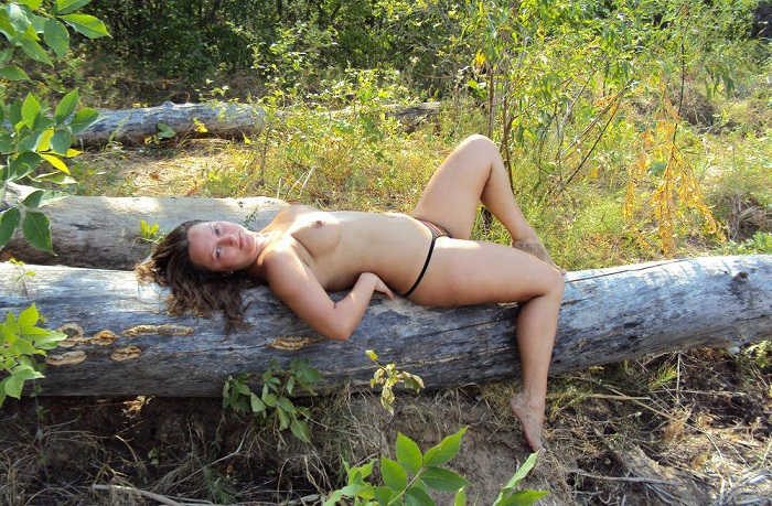 Сисястая брюнетка позирует на берегу реки - секс порно фото