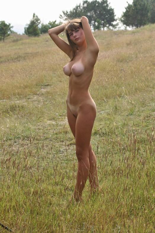 Голая милашка прогуливается по полю - секс порно фото
